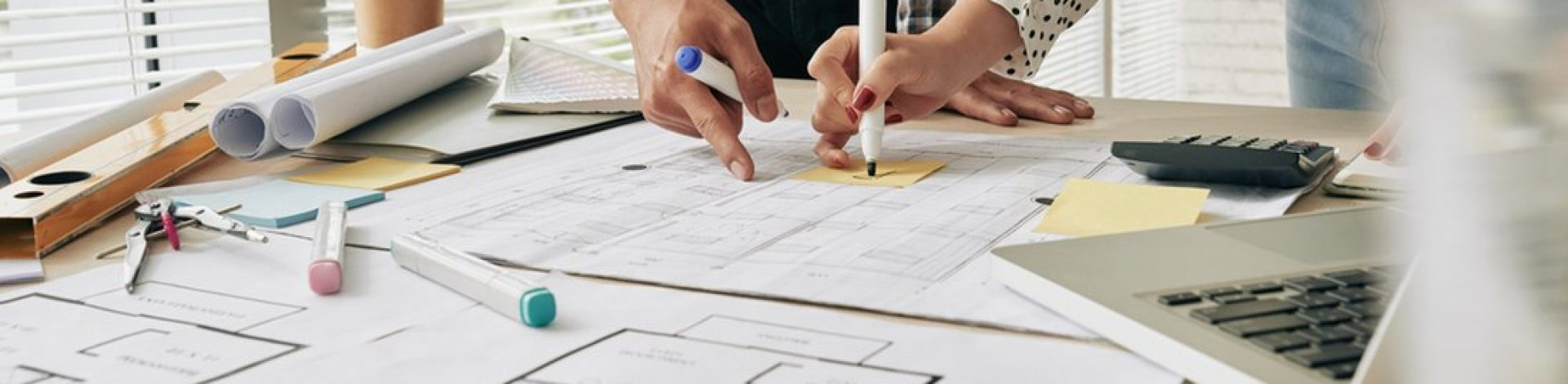 Close-up image of architects working on building blueprint